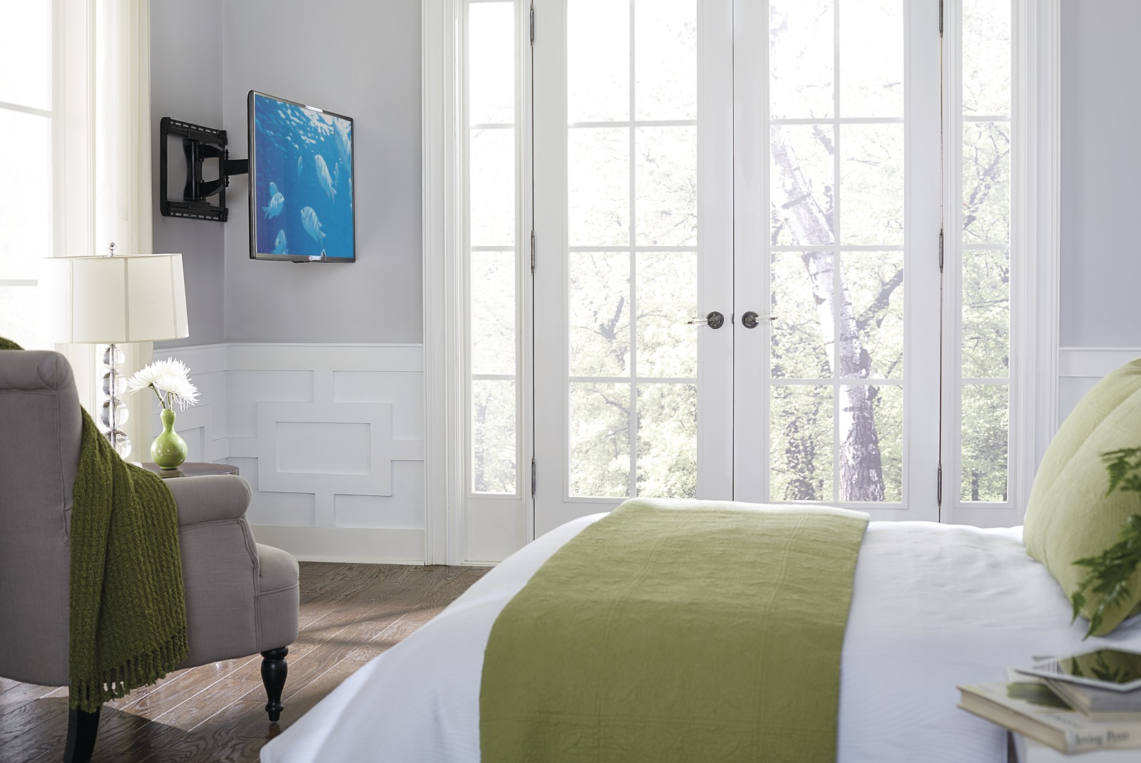 TV mounted in corner of bedroom